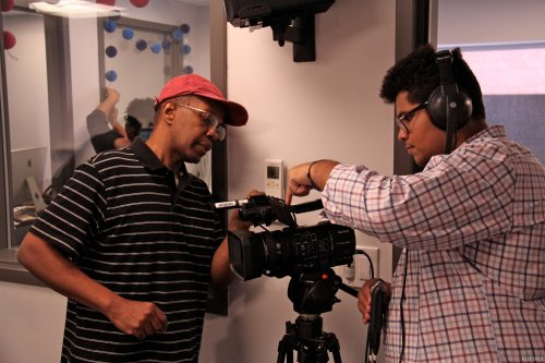 Intern being instructed on video camera recording.