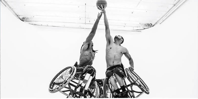 photo- 2 wheelchair basketball players reaching for the ball